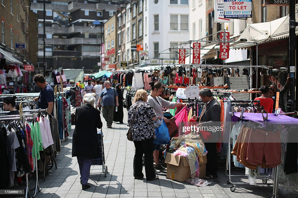 Shoppers peruse the stalls of Petticoat Lane Market on July 12, 2013 in London, England. Petticoat Lane Market is a historic clothing market in East London with records of trading on the site dating from around the year 1600.