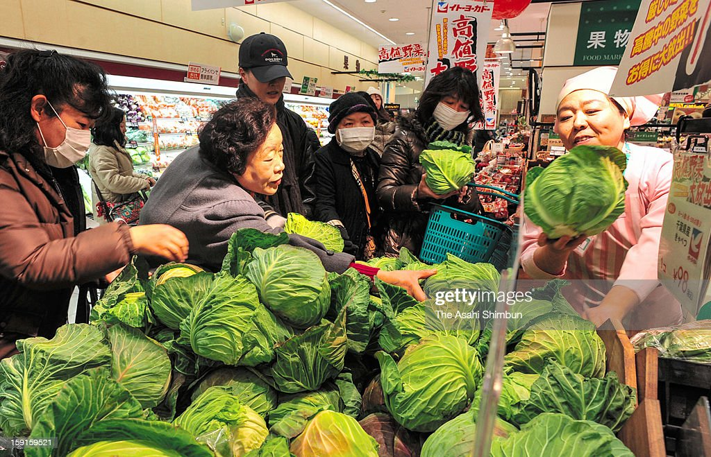 Shoppers pick up cabbages that is 60 percent cheaper than regular price at Ito Yokado supermarket on Janaury 9, 2013 in Tokyo, Japan. The cold weather caused price rise, especially leaf vegetable price is 20-40 percent higher than usual.