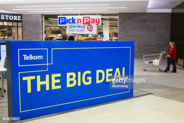 Shoppers push a cart past an advertisement for Telkom SA SOC Ltd outside a Pick n Pay Stores Ltd supermarket in a retail mall in Johannesburg South...