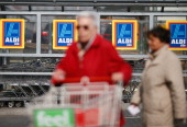 Shoppers push a shopping cart outside an Aldi store on April 8 2013 in Ruesselsheim near Frankfurt Germany Aldi which today is among the world's most...