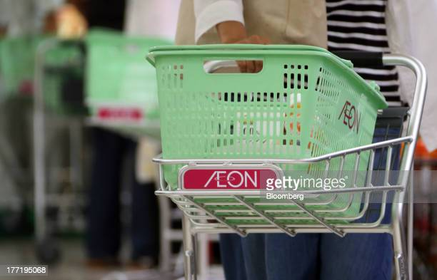 Shoppers push carts at an Aeon Co supermarket during a sale jointly held with Daiei Inc at an Aeon supermarket in Tokyo Japan on Thursday Aug 22 2013...