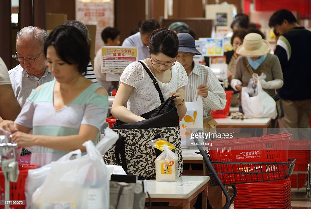 Shoppers put their purchased goods into shopping bags at a Daiei Inc. supermarket during a sale jointly held with Aeon Co. at a Daiei supermarket in Urayasu City, Chiba Prefecture, Japan, on Thursday, Aug. 22, 2013. Aeon's acquisition of 48.4 million Daiei shares will take place on Aug. 27 after the completion of tender offer yesterday, according to a statement to the Tokyo Stock Exchange released today. Photographer: Tomohiro Ohsumi/Bloomberg via Getty Images
