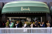 Shoppers queue ahead of the opening of the annual Harrods Summer Sale at Harrods on June 28 2014 in London England