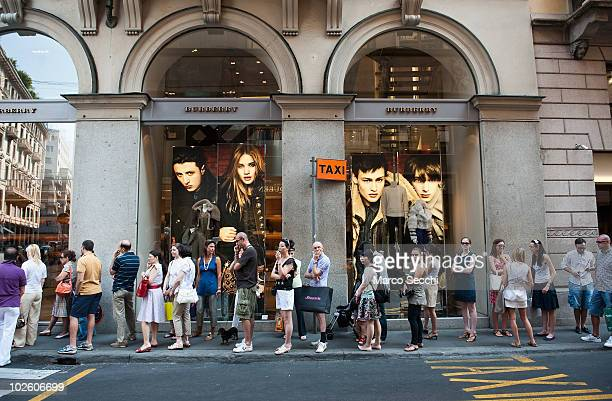 Shoppers queue in front of the Burberry's store in the fashion district of Milan on the first day of the Summer Sales on July 3 2010 in Milan Italy...