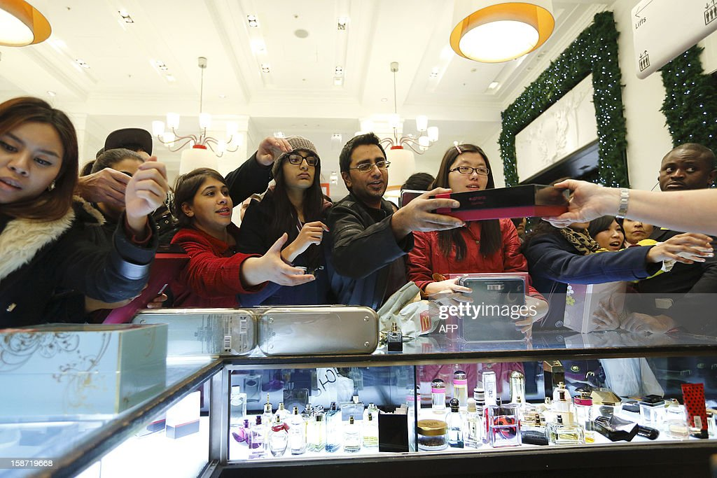 Shoppers reach out for discounted perfumes as they crowd inside the Selfridges department store in central London, on December 26, 2012, in search of a bargain during the post Christmas Boxing Day sales. Hundreds of thousands of bargain hunters headed to the shops for the traditional Boxing Day sales despite strike action on London's underground train network. AFP PHOTO / JUSTIN TALLIS