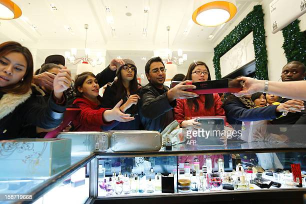 Shoppers reach out for discounted perfumes as they crowd inside the Selfridges department store in central London on December 26 in search of a...