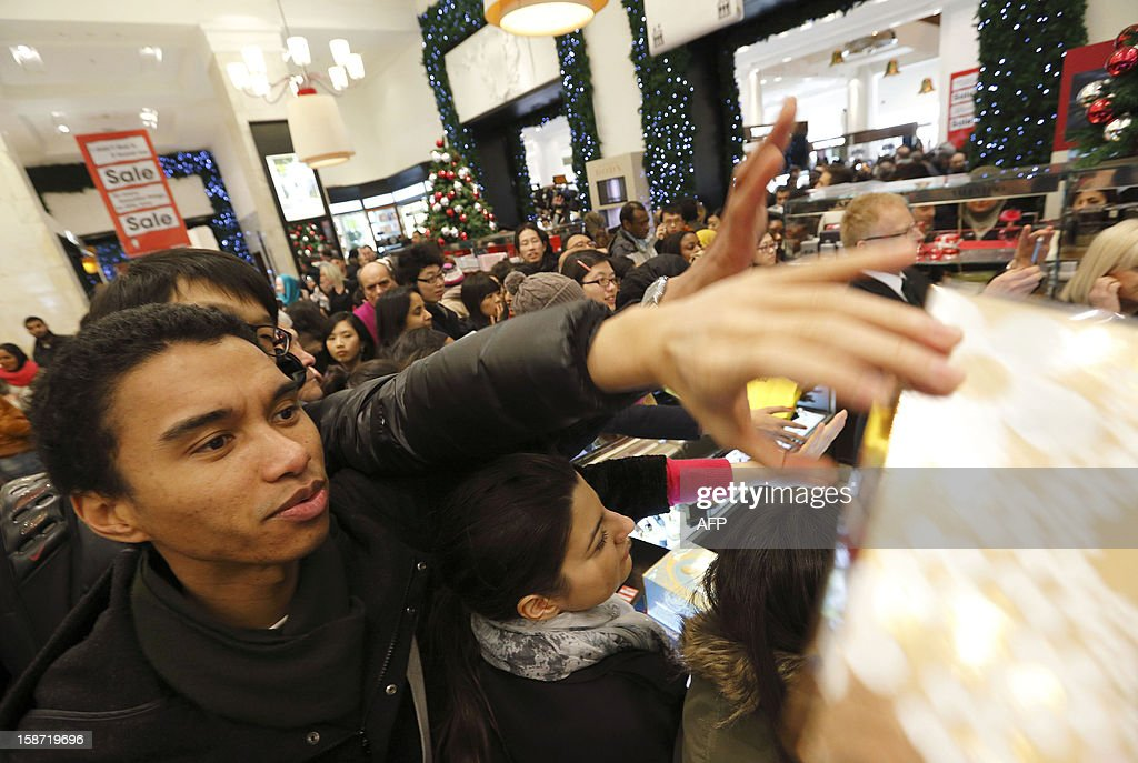 Shoppers reach out for discounted perfumes as they crowd inside the Selfridges department store in central London, on December 26, 2012, in search of a bargain during the post Christmas Boxing Day sales. Hundreds of thousands of bargain hunters headed to the shops for the traditional Boxing Day sales despite strike action on London's underground train network.