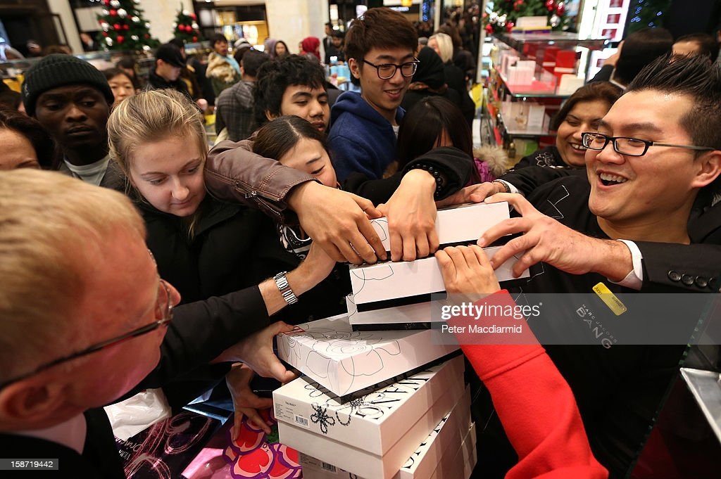 Shoppers reach out to grab a bargain at a perfume counter as a sales person (R) arrives with new stock at Selfridges department store on December 26, 2012 in London, England. Thousands of shoppers are in London looking for a bargain in the traditional Boxing Day sales.