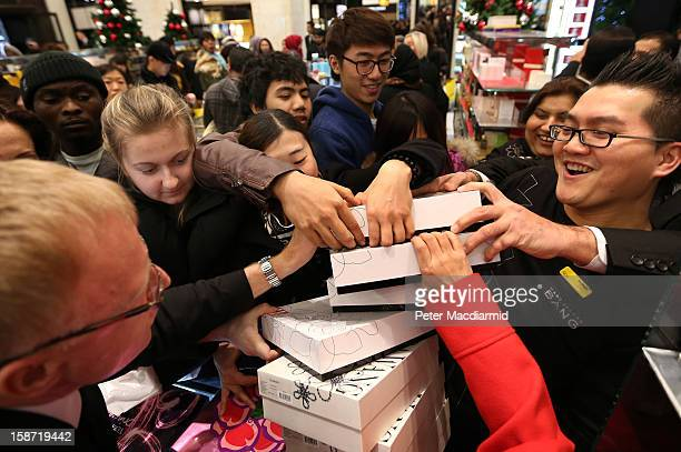 Shoppers reach out to grab a bargain at a perfume counter as a sales person arrives with new stock at Selfridges department store on December 26 2012...