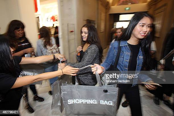 Shoppers receive shopping bags from staff members as they enter the store at the opening of the first HM Australia store at the GPO on April 5 2014...