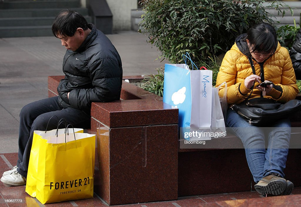 Shoppers rest on benches in the East Nanjing Road shopping area of Shanghai, China, on Friday, Feb. 1, 2013. China's services industries grew at the fastest pace since August as gains in retailing and construction aid government efforts to drive a recovery in the world's second-biggest economy. Photographer: Tomohiro Ohsumi/Bloomberg via Getty Images