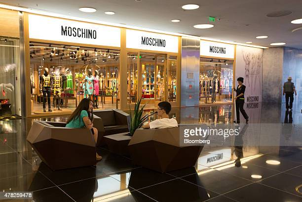 Shoppers rest outside a Moschino SpA fashion store while a cleaner sweeps the floor at the Esentai luxury shopping mall in Almaty Kazakhstan on...