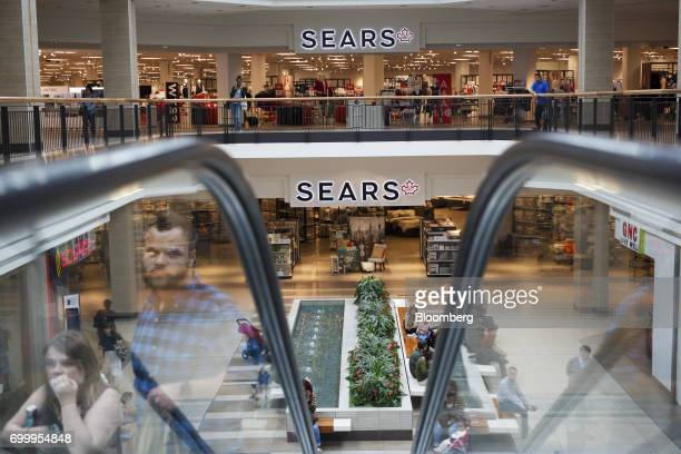 Shoppers ride an escalator in front of a Sears Canada Inc store inside a mall in Toronto Ontario Canada on Thursday June 22 2017 Canadian retailer...