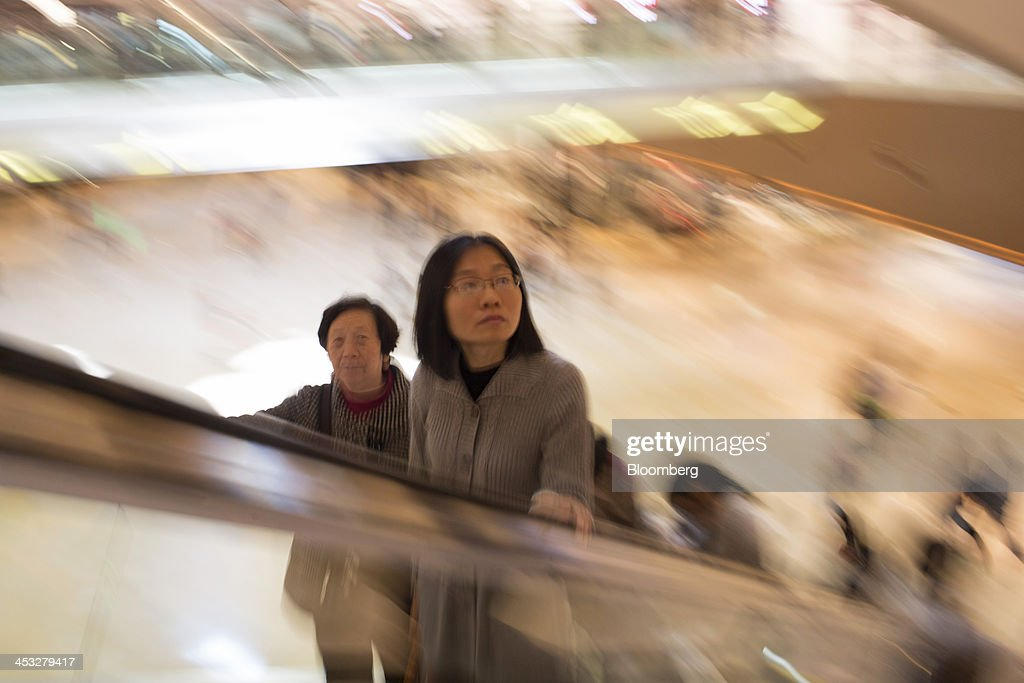 Shoppers ride an escalator inside the TaiKoo Hui shopping mall, operated by Swire Properties Ltd., in Guangzhou, China, on Saturday, Nov. 30, 2013. China's government may set its 2014 growth target at 7 percent, the Economic Information Daily reported on Dec. 3, citing the State Information Center. This compares with a goal of 7.5 percent for this year. Photographer: Brent Lewin/Bloomberg via Getty Images
