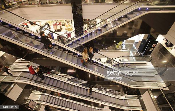 Shoppers ride on escalators in a Debenhams Plc store at Westfield London shopping mall operated by Westfield Group in London UK on Tuesday April 24...
