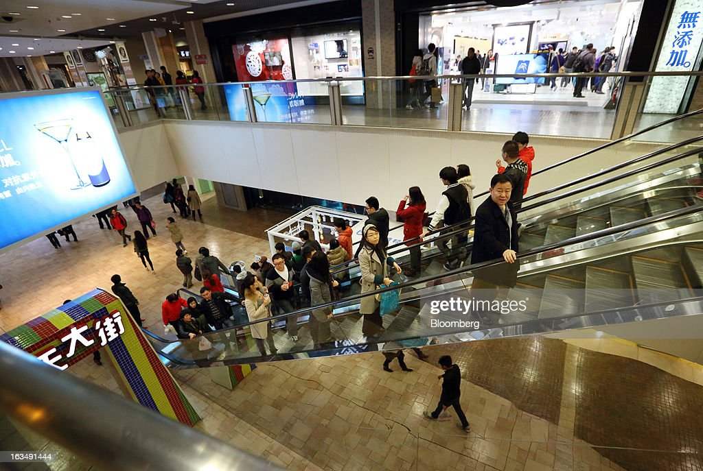 Shoppers ride on escalators in a shopping mall in the Wangfujing shopping district of Beijing, China, on Sunday, March 10, 2013. China's industrial output had the weakest start to a year since 2009 and lending and retail sales growth slowed, toughening challenges for a new leadership that wants to narrow the gap between rich and poor. Photographer: Tomohiro Ohsumi/Bloomberg via Getty Images