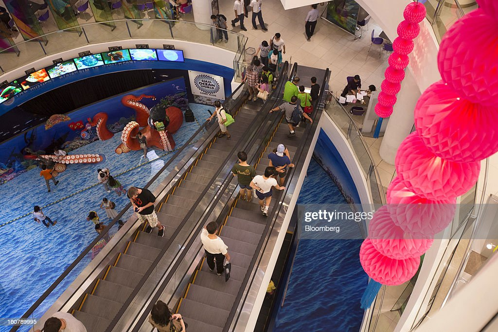 Shoppers ride on escalators inside the Siam Paragon shopping mall in Bangkok, Thailand, on Tuesday, Feb. 5, 2013. Thai inflation may average 2.8 percent this year, the Bank of Thailand said. Photographer: Brent Lewin/Bloomberg via Getty Images