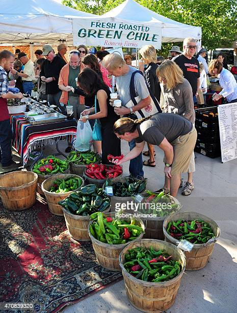 Shoppers select red and green chile peppers for sale at the popular vegetable market in Santa Fe New Mexico
