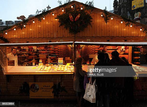 Shoppers shelter at a Dutch cheese stall at the European Christmas market in Manchester northwest England on December 22 2009 AFP PHOTO/PAUL ELLIS