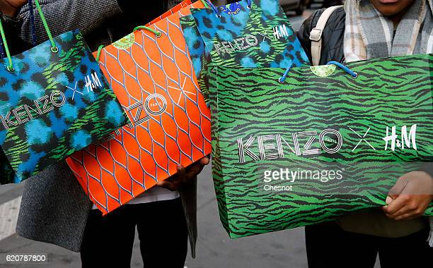 Shoppers show bags with the Kenzo logo at HM Haussmann store opening at 8 am for the Launch of the Kenzo x HM collection in Paris at HM Boulevard...