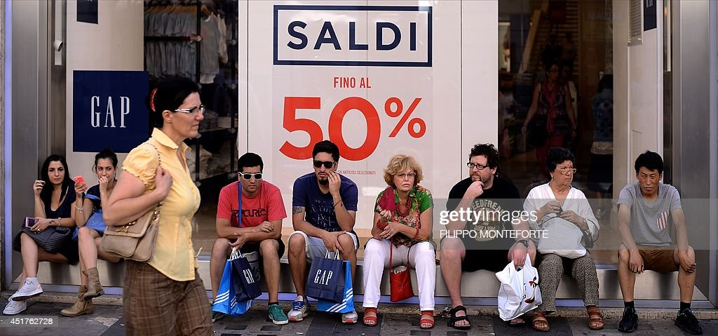 Shoppers sit in front a shop window advertising sale on July 6, 2014 in downtown Rome, as Italian retailers started their summer sales.