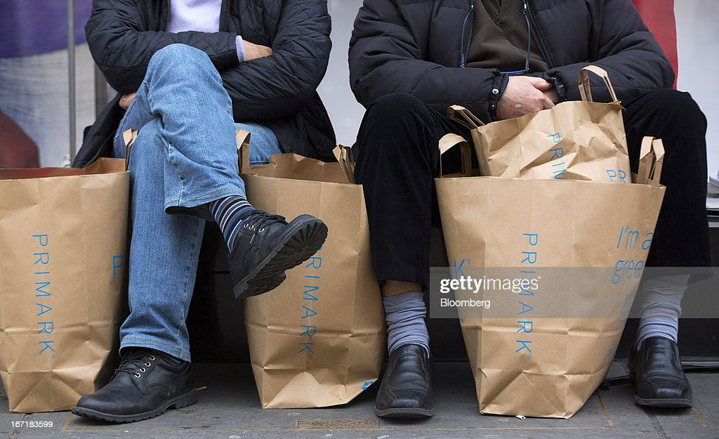 Shoppers sit with their shopping bags outside a Primark store on Oxford Street in central London, U.K., on Monday, April 22, 2013. Associated British Foods Plc, the owner of the Primark discount-clothing chain, fell the most in three months after Credit Suisse Group AG said it's unlikely the chain's profit growth can continue at the first half's pace. Photographer: Jason Alden/Bloomberg via Getty Images