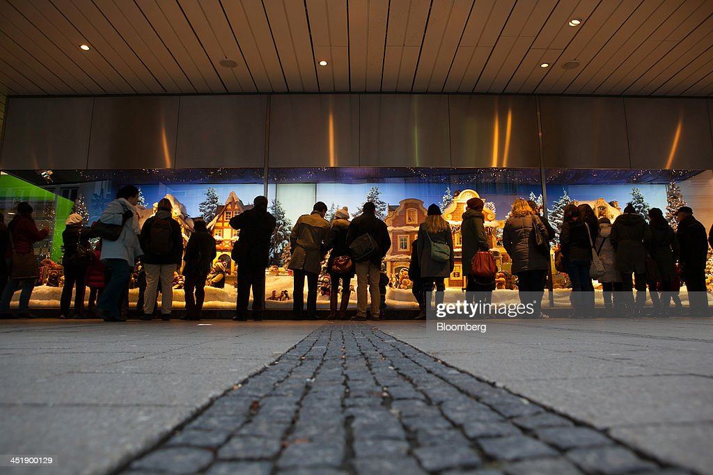 Shoppers stand and look at a Christmas window display at a Karstadt Warenhaus GmbH department store in Munich, Germany, on Sunday, Nov. 24, 2013. In Germany, Europe's biggest economy, annual consumer prices increased 1.2 percent in October. Photographer: Krisztian Bocsi/Bloomberg via Getty Images
