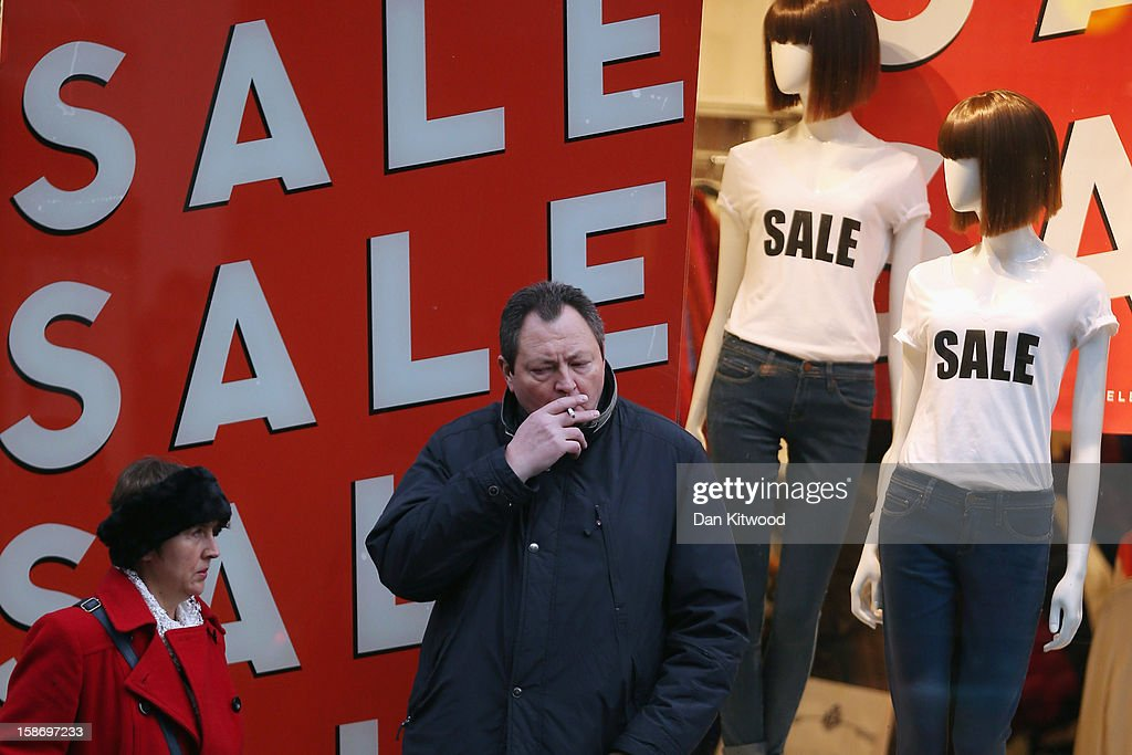 Shoppers stand outside the shop window of a fashion shop advertising their pre-Christmas sales on Oxford Street on December 24, 2012 in London, England. Many high street retailers have started their sales two days early this year on what is expected to be the busiest shooping day of the year.