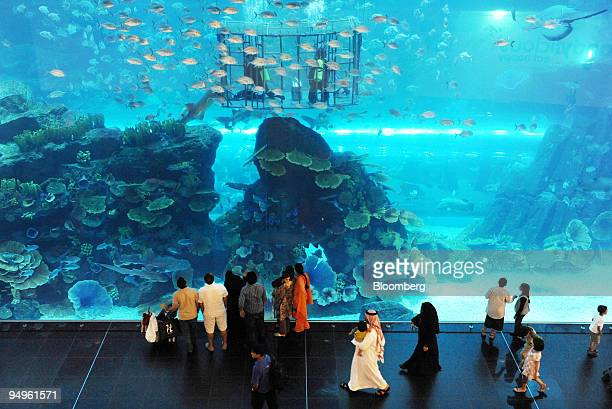 Shoppers stop to look at the aquarium in the Dubai Mall owned by Emaar Properties PJSC in Dubai United Arab Emirates on Sunday July 12 2009 The mall...