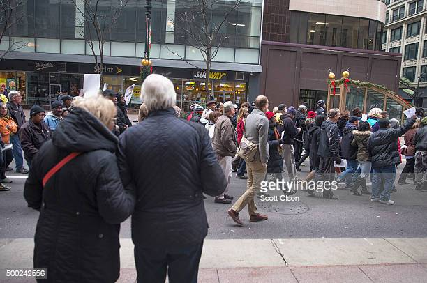 Shoppers stop to watch as demonstrators led by Rev Jesse Jackson march down State Street to protest the death of Laquan McDonald and the alleged...