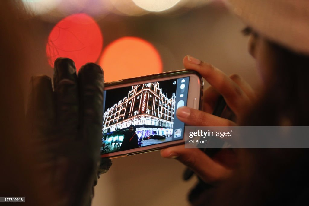 Shoppers take photographs of Harrods department store in Knightsbridge on November 29, 2012 in London, England. Many prominent retailers in the capital have produced elaborate festive window displays to entice Christmas shoppers with less than one calendar month remaining before Christmas Day.