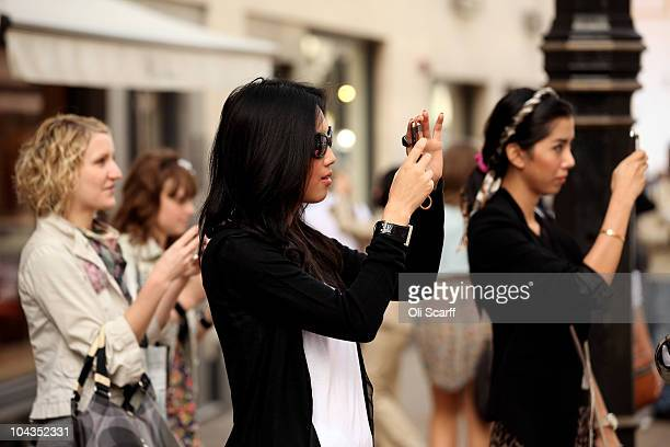 Shoppers take photographs of the window display of the Louis Vuitton shop on New Bond Street in Mayfair which is the most expensive avenue in Europe...