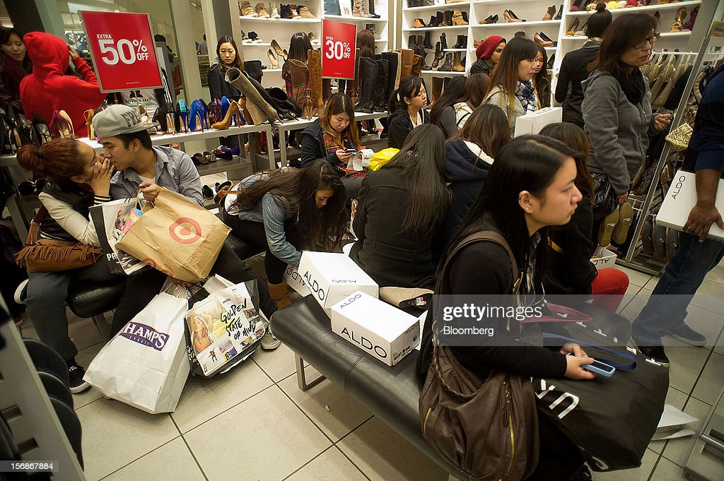 Shoppers try on shoes inside an Aldo Group Inc. shoe store in the Westfield San Francisco Centre mall in San Francisco, California, U.S., on Friday, Nov. 23, 2012. To get shoppers to spend more than last year, retailers have continued to turn Black Friday, originally a one-day event after Thanksgiving, into a week's worth of deals and discounts. Photographer: David Paul Morris/Bloomberg via Getty Images