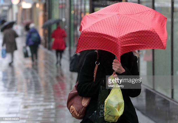 Shoppers use umbrellas to shelter from the rain as they make their way along a street on January 3 2012 in Bristol England High winds have been...