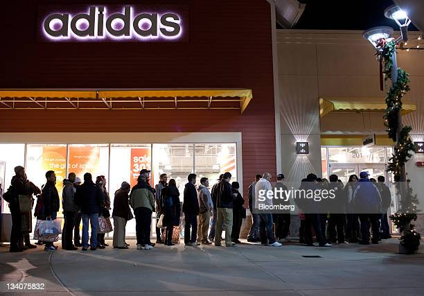 Shoppers wait in line for the opening of the Adidas AG store at the Premium Outlet Mall in Tinton Falls New Jersey US on Thursday Nov 24 2011...