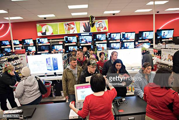 Shoppers wait in line to pay for items in the electronics department at a Target Corp store ahead of Black Friday in Mentor Ohio US on Thursday Nov...
