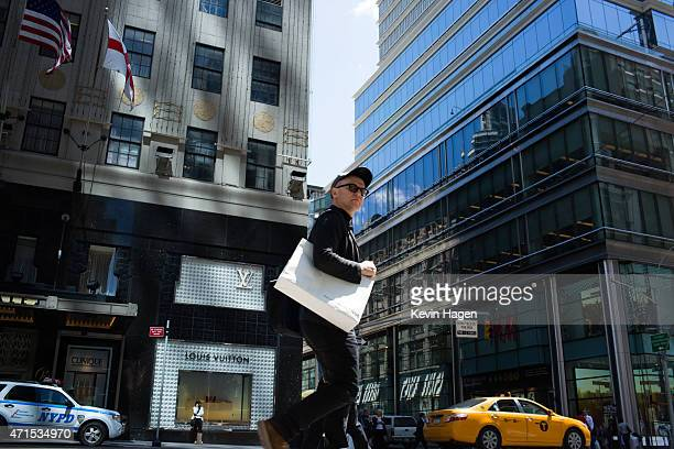Shoppers walk along Lexington Avenue in the eastern Midtown section of Manhattan on April 29 2015 in New York City According to the Federal Reserve...