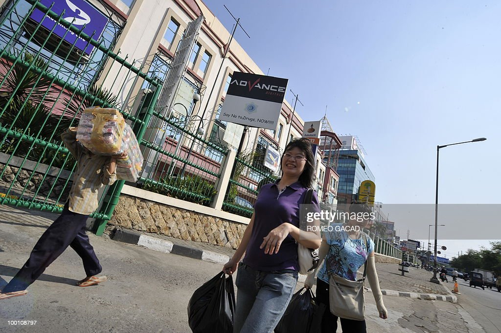 Shoppers walk along the commercial center in Glodok district in Jakarta on May 21, 2010
