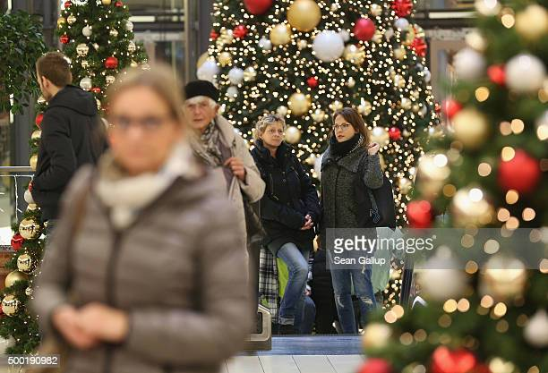 Shoppers walk among Christmas trees in a shopping mall on a shopping Sunday on December 6 2015 in Berlin Germany Stores are usually closed on Sundays...