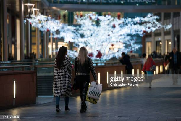 Shoppers walk among the Christmas lights as shops and businesses in Liverpool hope of an early boost to sales during the festive period on November...