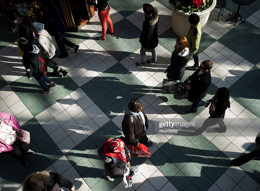 Shoppers walk around the Easton Towne Center in Columbus, Ohio, U.S., on Friday, Nov. 29, 2013. About 97 million people planned to shop online or in stores on Black Friday, with about 140 million intending to do so yesterday through Sunday, the National Retail Federation said. Photographer: Ty Wright/Bloomberg via Getty Images