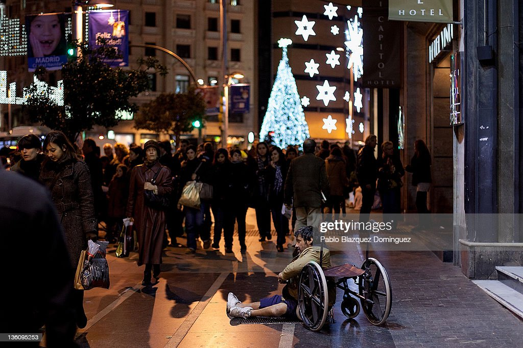 Shoppers walk by a dissable man begging near Plaza Callao six days before Christmas Day on December 19, 2011 in Madrid, Spain. This year businesses are starting sales and discounts before Christmas to try and gain customers during the current economic crisis.