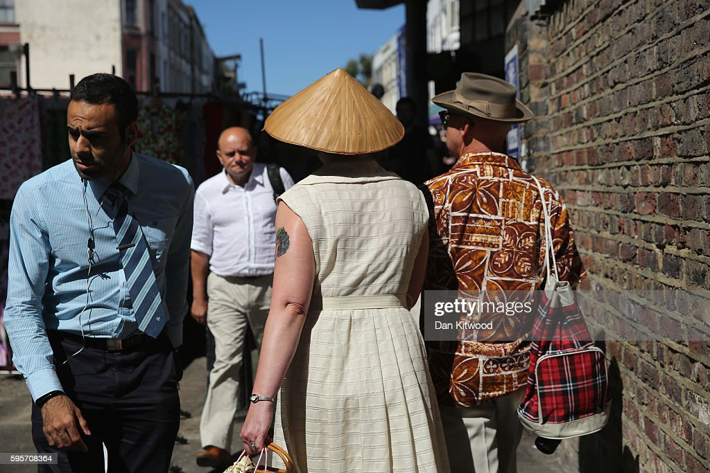 Shoppers walk down Portobello Road on August 26 2016 in London England Many shops businesses and residential properties are boarded up to prevent...