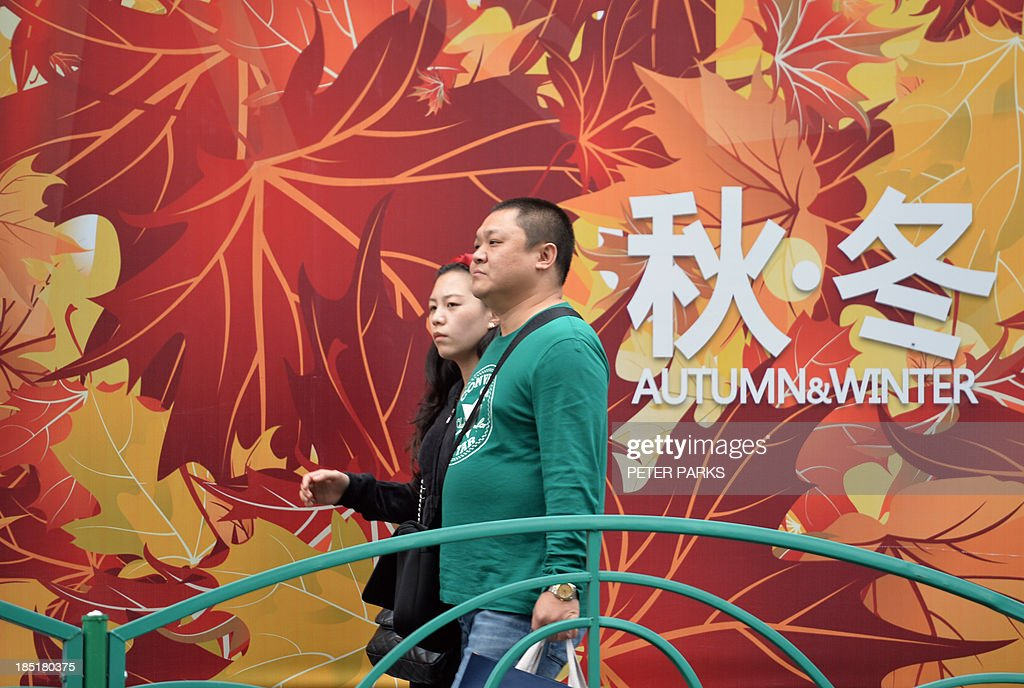 Shoppers walk in a commercial district of Shanghai on October 18, 2013. China's economy expanded 7.8 percent year-on-year in July-September, data showed, snapping two quarters of slowing growth, but analysts questioned whether the improvement was sustainable.AFP PHOTO/Peter PARKS