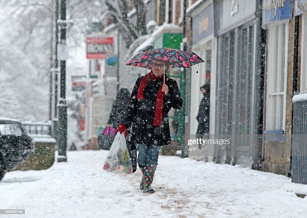 Shoppers walk in the high street after heavy snowfall in Guisborough, north east England, on January 15, 2013. Heavy snowfall has hit parts of central and north east England, bringing sub-zero temperatures and travel disruption across the country. AFP PHOTO / LINDSEY PARNABY