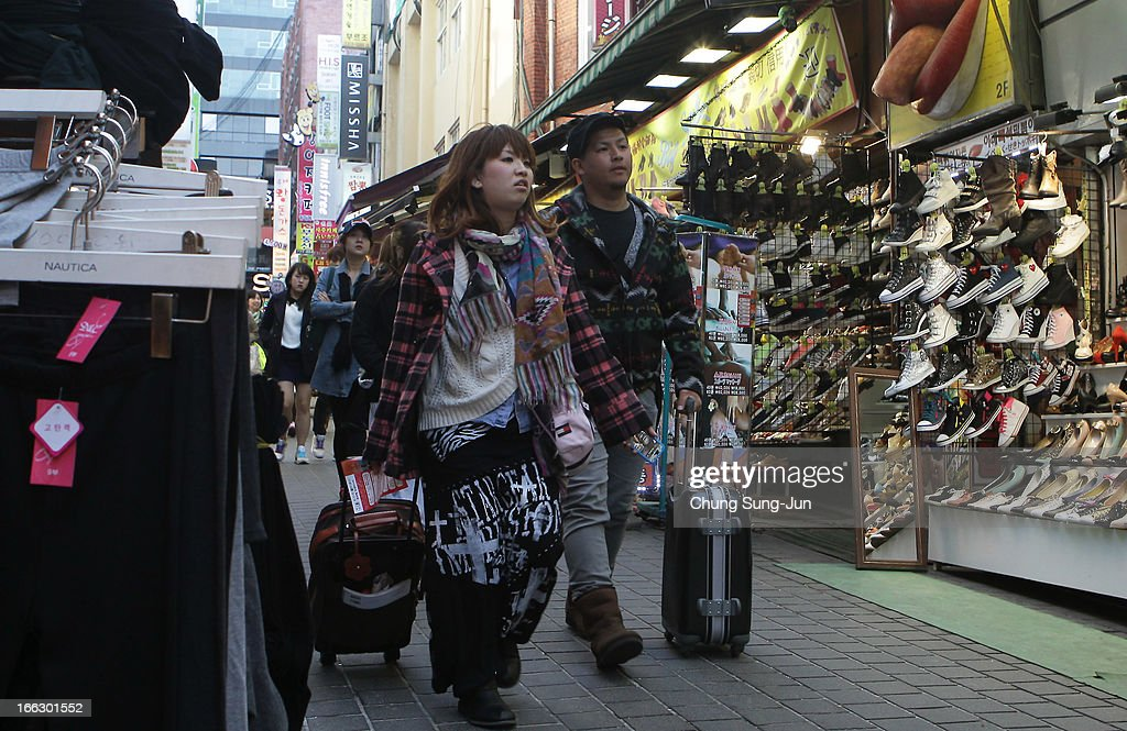Shoppers walk in the Myungdong shopping district on April 11, 2013 in Seoul, South Korea. According to reports a North Korean missile launcher has been moved into firing position as the continuing threats of attack emit from Pyongyang. G8 leaders have convened in London to discuss the situation..