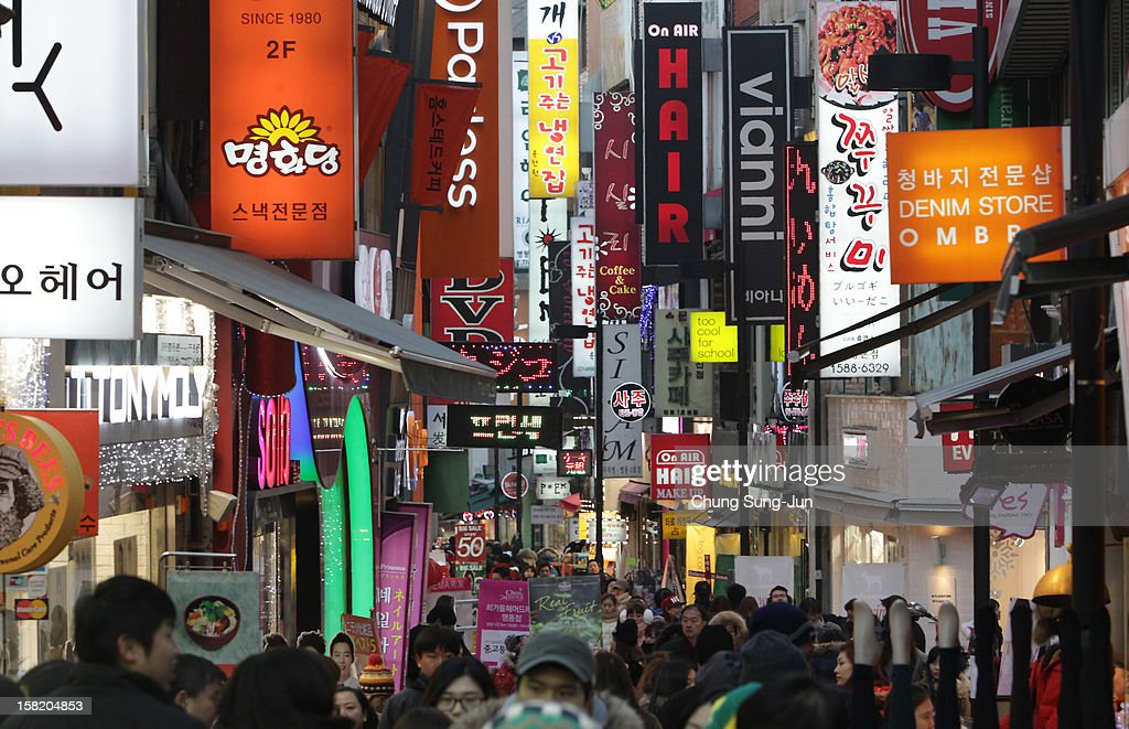 Shoppers walk in the Myungdong shopping district on December 11, 2012 in Seoul, South Korea. One of the main South Korean presidential election campaign issues is the economy, as the chaebol, South Korea's business conglomerate, dominates the country's wealth while the economic life of middle class people has not been improving.