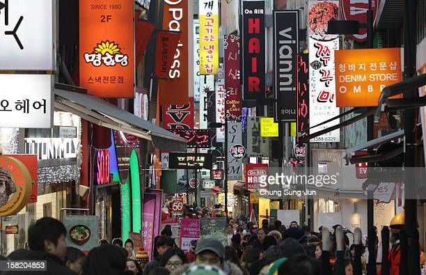 Shoppers walk in the Myungdong shopping district on December 11 2012 in Seoul South Korea One of the main South Korean presidential election campaign...