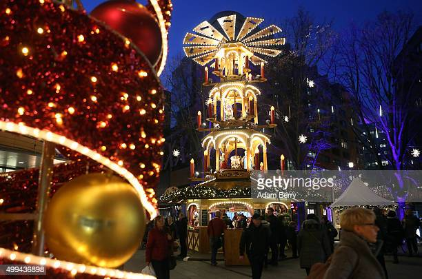 Shoppers walk outside a shopping mall on December 1 2015 in Berlin Germany German consumer morale and willingness to spend showed signs of declining...