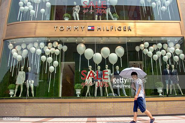 Shoppers walk past a 30% discount sale sign on a shop window The consumer inflation rate in China rose to 14 percent in June though higher than 12...